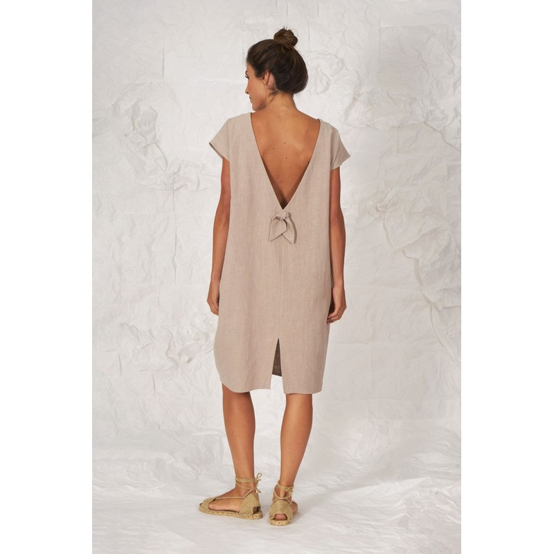 Vestido de lino beige con manga caída, bolsillos laterales, espalda en V con detalle y pequeña lazada.